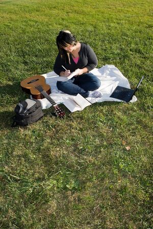 A young musician writing in her notebook while sitting in the grass on a nice day. Imagens