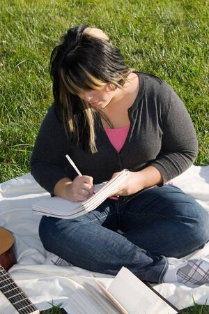 A young musician writing in her notebook while sitting in the grass on a nice day. photo