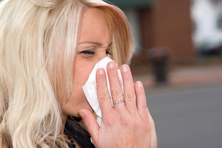 This young woman sneezing into a tissue either has a cold or really bad allergies. Stock Photo - 4190549