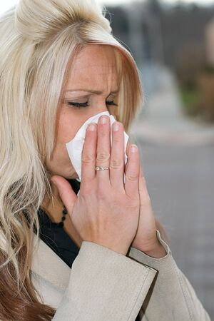 either: This young woman sneezing into a tissue either has a cold or really bad allergies. Stock Photo