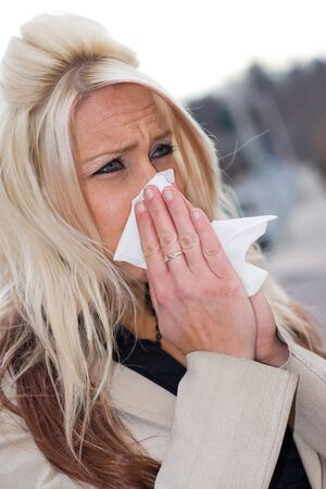 This young woman sneezing into a tissue either has a cold or really bad allergies. Stock Photo - 4220175
