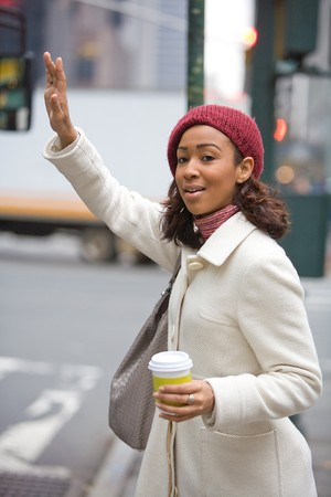 A pretty young business woman hails a taxi cab in the city.