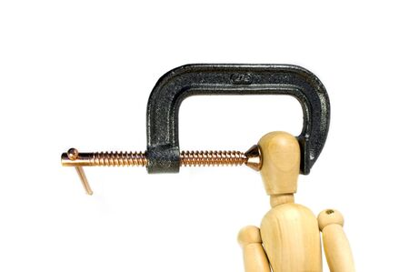 c clamp: A clamp squeezing tightly on the head of a wooden man.  A great concept shot for headaches or stress.