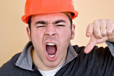 This construction worker is pointing and yelling his head off at someone. photo