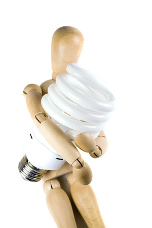 A wooden model grasping a compact fluorescent light bulb.  Great for energy savings or going green concepts. Stock Photo - 4288535