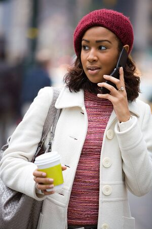 An attractive business woman talking on her cell phone along with a hot coffee. photo