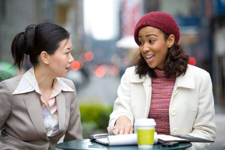 Two business women having a casual meeting or discussion in the city.  Stock Photo - 4288546