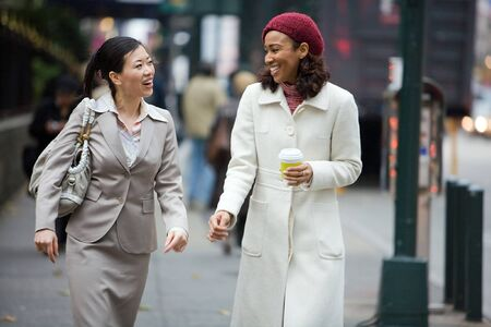 sidewalk talk: Two business women having a conversation while walking in the big city.