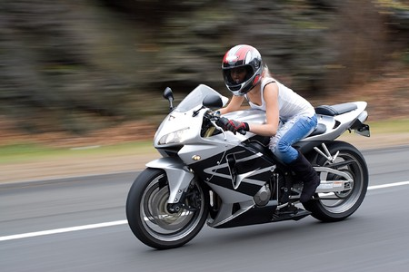 Abstract blur of a pretty girl driving a motorcycle at highway speeds. Stock Photo - 4324279
