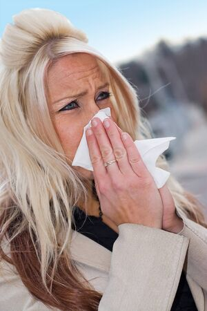 This young woman sneezing into a tissue either has a cold or really bad allergies. photo
