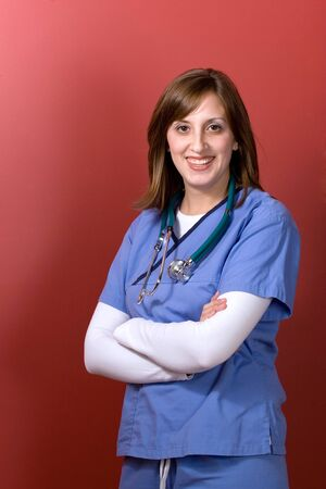 A young woman doctor with her arms crossed isolated over a red background photo