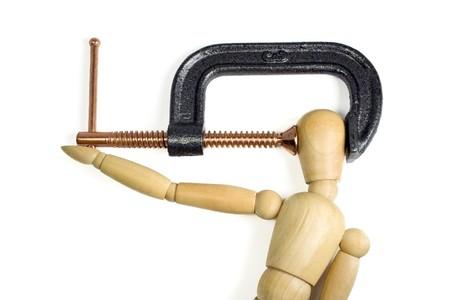 Drücken einer Klemme fest auf den Kopf eines Mannes aus Holz. Ein großer Schuss Konzept für Kopfschmerzen oder Stress.