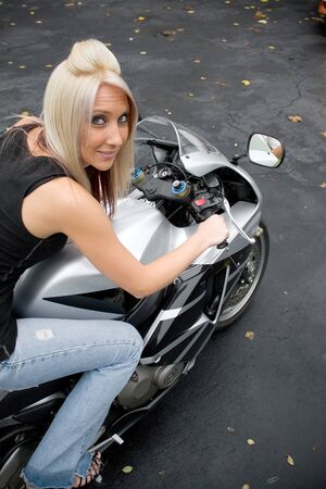 bombshell: A young blonde woman poses on her motorcycle.