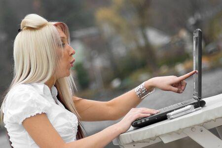 pornografia: Una bella mujer joven rubia puntos para su port�til de pantalla en asombro. Parece como si ella es ver algo ofensivo.