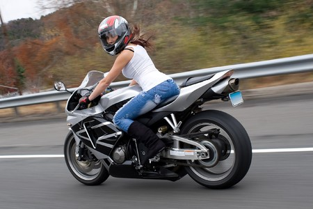 hottie: A pretty blonde girl in action driving a motorcycle at highway speeds.