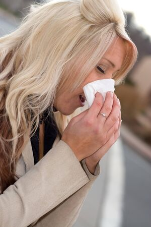 This young woman sneezing into a tissue either has a cold or really bad allergies. Stock Photo - 4338157