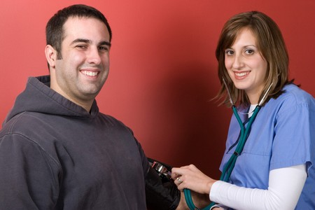 A young nurse checks the blood pressure of her patient. photo
