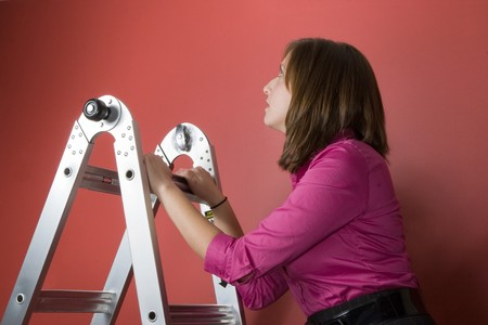 A young business woman rising to the top of this symbolic corporate ladder. Stock Photo - 4338134