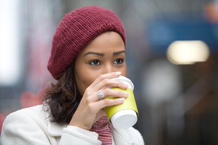 An attractive business woman enjoying a hot coffee in the city. Stock Photo
