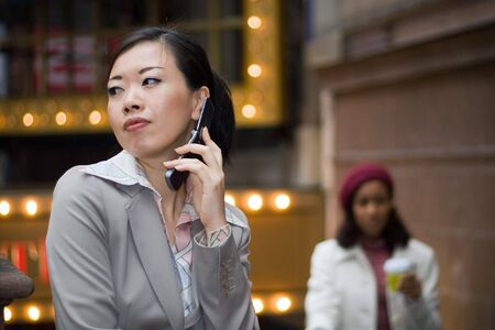 An attractive Asian business woman talking on her cell phone in the city. Stock Photo - 4358534
