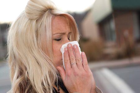 alergenos: Esta joven mujer de estornudar en un pa�uelo de papel o bien tiene un resfriado o alergias muy mal.