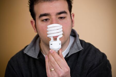A young man holding an energy saving compact fluorescent light bulb.  Shallow depth of field with stronger focus on the bulb. photo
