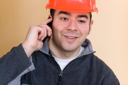 A young construction professional talks on his smartphone. photo