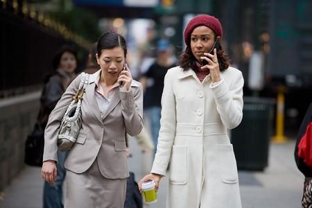 mobiele telefoons: Twee vrouwen die een zakelijke gesprekken op hun mobiele telefoons tijdens het wandelen in de grote stad.