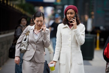 mobile communication: Two business women having conversations on their cell phones while walking in the big city.