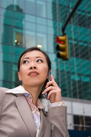 An attractive Asian business woman talking on her cell phone in the city. Stock Photo - 4374769