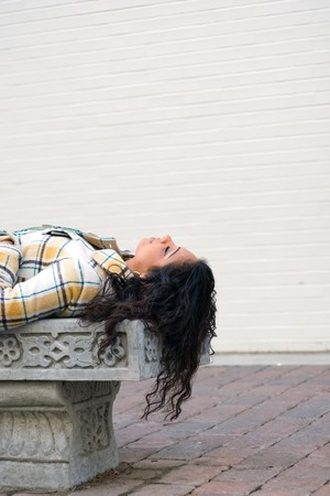 A closeup of a pretty Indian woman laying on a bench outdoors. Stock Photo - 4374783