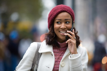 An attractive business woman talks on her cell phone as she walks through the city. photo