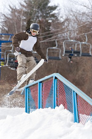 performs: A young man performs a rail slide on skis. Slight motion blur.