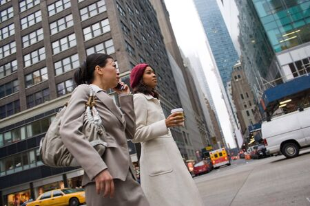 sidewalk talk: Two business women walking in the big city. One woman is on her cell phone.  Slightly shallow depth of field.