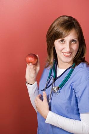 Una joven enfermera est� sosteniendo una manzana. Una manzana al d�a mantiene al m�dico alejado. Foto de archivo - 4421583