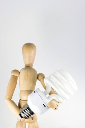 grasping: A wooden model grasping a compact fluorescent light bulb.  Great for energy savings or going green concepts.