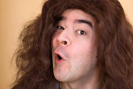 A model with really long hair has a funny expression on his face. photo
