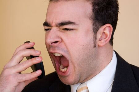 A business man is furiously screaming into his cell phone. Stok Fotoğraf
