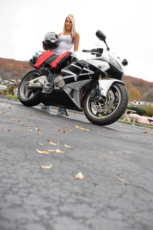 hottie: A pretty blonde posing with her motorcycle and riding gear.  Lots of copyspace.