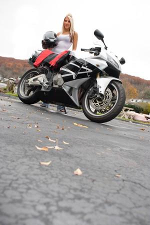 Ein ziemlich blond posiert mit ihrem Motorrad und Reiten Gang. Viele copyspace. Standard-Bild - 4444746