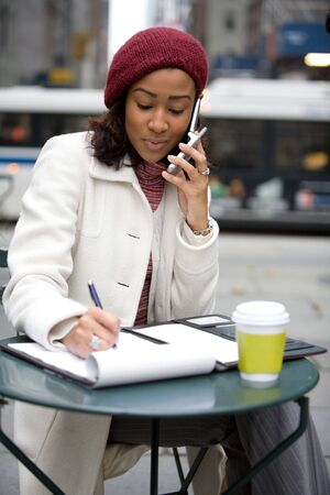 An attractive business woman talking on her cell phone and writing something down in her notes. Stock Photo - 4444749