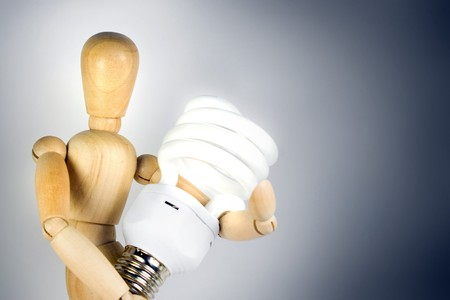 A wooden model grasping a compact fluorescent light bulb.  Great for energy savings or going green concepts. photo