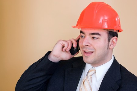 A man in a business suit and hard hat talks on his cell phone.  He could be a custom home builder or even an engineer or architect. photo