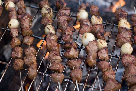 Beef shish kebab skewers cooking over a hot camp fire. photo