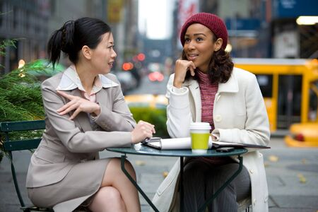chinese american: Two business women having a casual meeting or discussion in the city.  Stock Photo