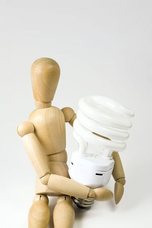 A wooden model grasping a compact fluorescent light bulb.  Great for energy savings or going green concepts. Stock Photo - 4525655