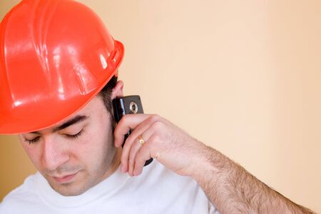 A young construction worker talks on his smartphone.  Plenty of copyspace for your text or images. photo