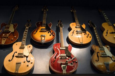 A wall with vintage guitars hanging on display.