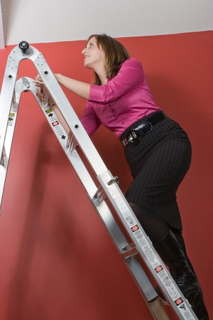 A young business woman rising to the top of this symbolic corporate ladder. photo
