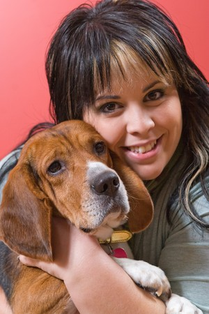 A pretty young woman posing with her beagle pup.  Shallow depth of field. Stock Photo - 4548541